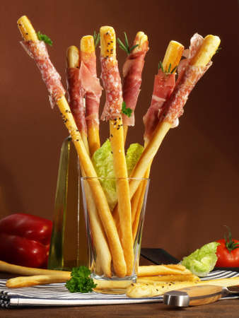 Grissini with Ham Appetizer on wooden background.