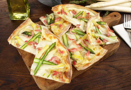 Traditional Tarte Flambee with Creme Fraiche, Onion, Asparagus and Bacon on wooden background.