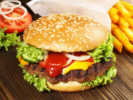 Grilled cheeseburger with French fries on wooden background.
