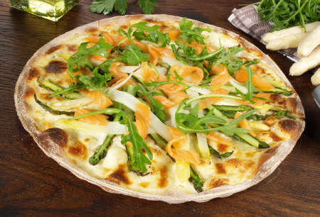 Traditional Tarte Flambee with Creme Fraiche, Onion, Asparagus and Salmon on wooden background.