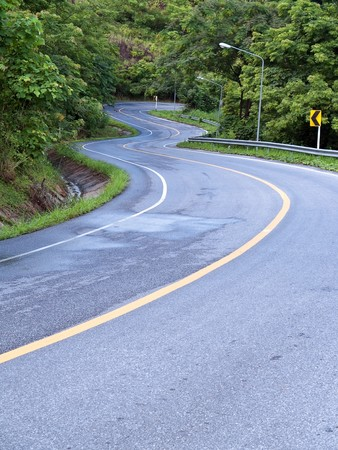 Road curves pass through the mountain and forest Stock Photo