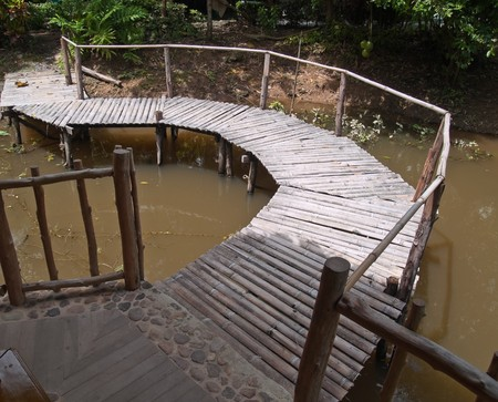 Old curved bamboo bridge cross over pool photo