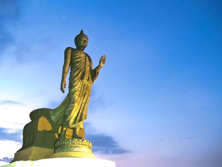 Walking Buddha image in Vitarka Mudra posture illuminate with spotlight at twilight time, Buddhamonthon, Nakhon Pathom, Thailand