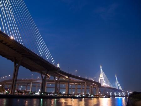 Bhumibol Bridge also casually call as Industrial Ring Road Bridge with floodgate illuminate with spotlight at night scene, Samut Prakarn, Thailand