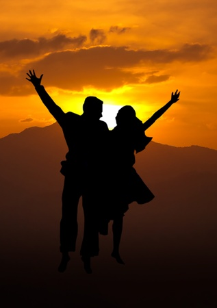 Silhouette of loving couple jumping on a hill against the sun and mountains range