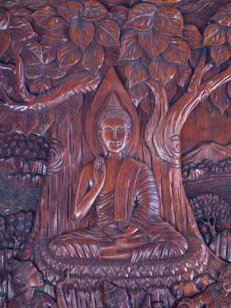 Wooden Buddha image carving by native Thai style decorate on temple door, Thailand photo