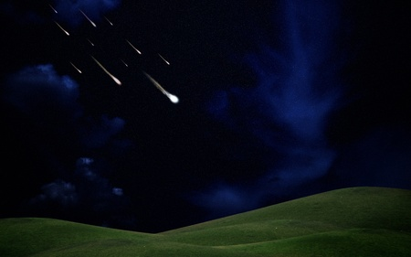 Falling stars on green hill  with darkness sky photo