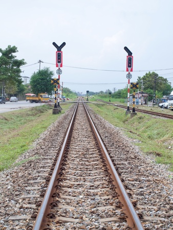 Railroad with crossing sign in countryside of Thailand