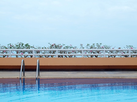 Swimming pool with blue water on terrace of condominium photo