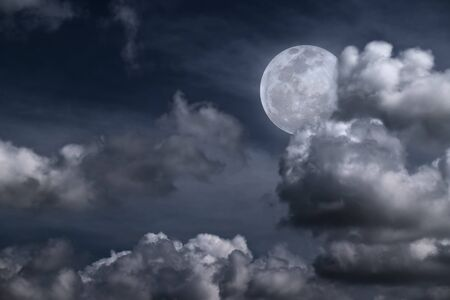 Beautiful full moon behind fantasy cloudy sky photo