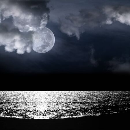 Beautiful full moon behind fantasy cloudy sky over water with reflection photo