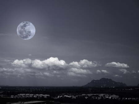 Full moon rises over the mountain and village photo