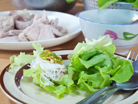 Thai style salad with leaf lettuce, noodle, slice boiling pork and spicy sauce photo