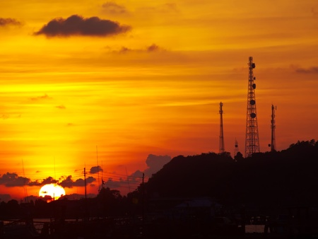 Golden sky with telecommunication tower on top of mountain photo