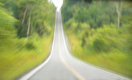 Uphill highway between forest in motion blur photo