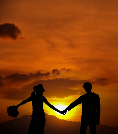 Silhouette of loving couple standing on a hill against the sun and mountains range photo