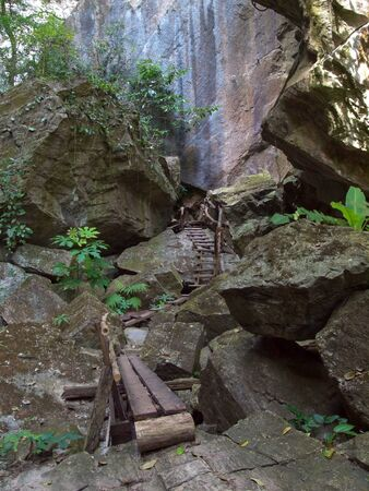 among: Footpath in valley among cliff on rainforest Stock Photo