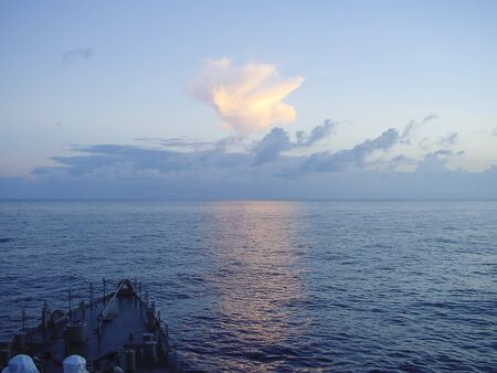 warship: Prow of warship sailing in ocean with beautiful sunlight on cloud Stock Photo