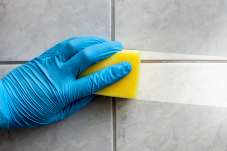 Cleaning sponge held in hand while cleaning bathroom Stock Photo