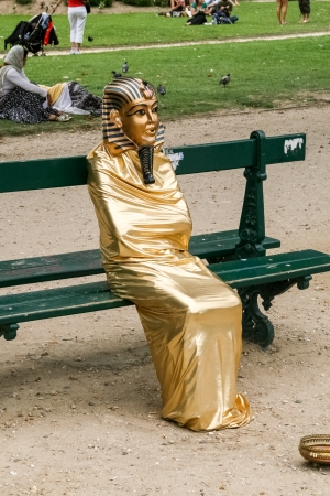 Paris, France, August 25th, 2013 - Street artist doing living statue of Egyptian pharaoh sitting on bench