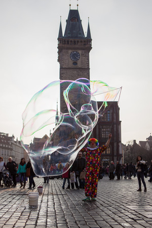 praga: PRAGUE, CZECH REPUBLIC - MARCH 8th, 2014 - Clown makes extra big bubbles on Old Town Square