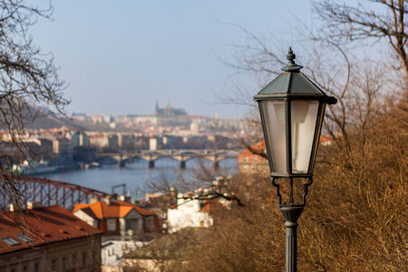 PRAGUE, CZECH REPUBLIC - MARCH 8th, 2014 - Street lamp with Prague Castle and Charles bridge on Vltava river in background