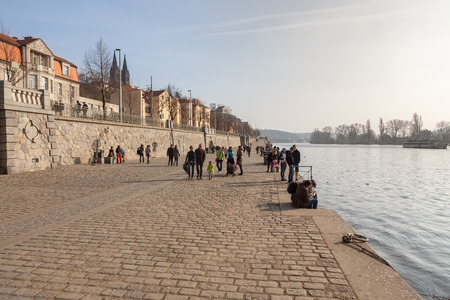 PRAGUE, CZECH REPUBLIC - MARCH 8th, 2014 - People walk on promenade of Vltava river