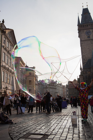 PRAGUE, CZECH REPUBLIC - MARCH 8th, 2014 - Clown makes extra big bubbles on Old Town Square