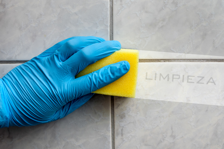 Cleaning sponge held in hand while cleaning bathroom with spanish lettering limpieza Foto de archivo