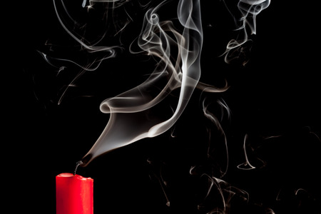 blow out: Smoke from blown out red candle on black backround