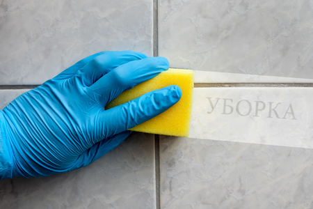 Cleaning sponge held in hand while cleaning bathroom with russian lettering (cleaning in english translation)