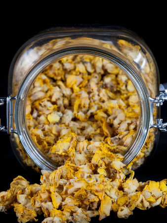 Jar full of dried mullein on black background photo
