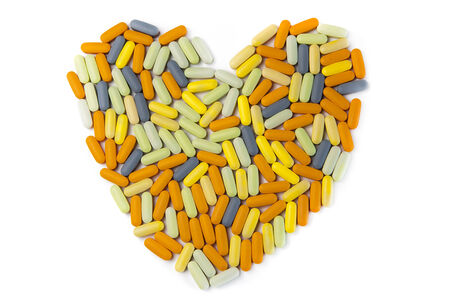 Medicine pills of various colors in shape of heart Stock Photo