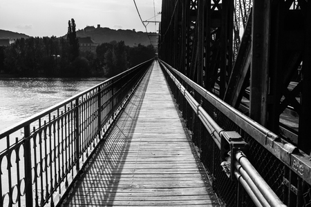 Path on industrial railroad and pedestrian bridge  leading to far away, black and white photo photo