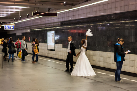 Prague, Czech Republic - 15th September, 2014: Wedding in subway station. Bride and groom take wedding photos in metro platform full of people waiting for train