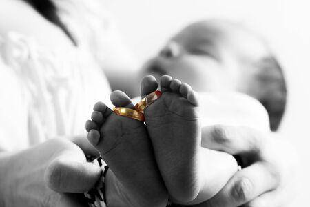 baby's feet: Golden wedding rings on newborn babys feet Stock Photo
