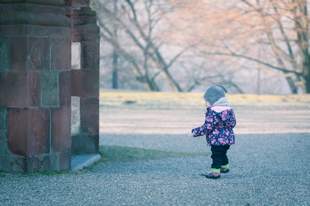 curiously: Little baby toddler curiously exploring outdoors world in winter Stock Photo