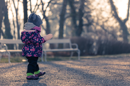 nosey: Little baby toddler curiously exploring park outdoors in winter Stock Photo