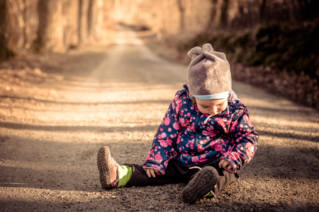 nosey: Little baby toddler sitting and playing on dirt road in winter evening