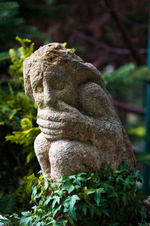 head stones: statue in the garden with a closed mouth symbolizing silence