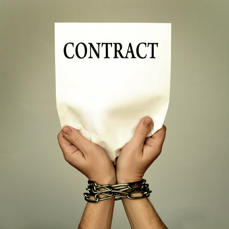 slave labor: man with bound hands to hold a contract. Stock Photo
