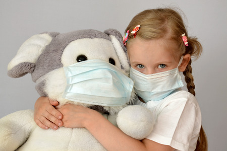 infected: portrait of a sick child in a medical mask with a soft toy