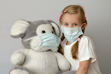 portrait of a sick child in a medical mask with a soft toy
