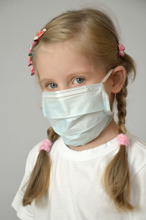 portrait of a sick child in a medical mask