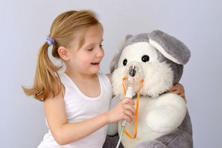 Child, kid (girl) with an inhaler (nebulizer) makes the procedure a soft toy.