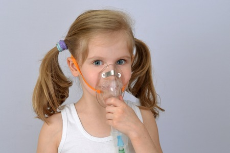 Child, kid (little girl) with inhaler (nebulizer) makes the procedure.