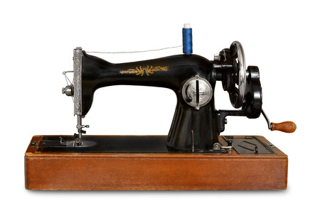 old sewing machine with manual drive on white isolated background Stock Photo