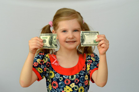 Baby girl holds in hands a torn banknote, dollar, banking crisis.