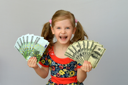 little girl holding in hands a pack of dollars and Euro