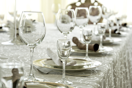 Clean dishes, glasses and plates on the table in the restaurant. Stock Photo